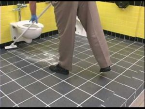 cleaner mopping floor in washroom
